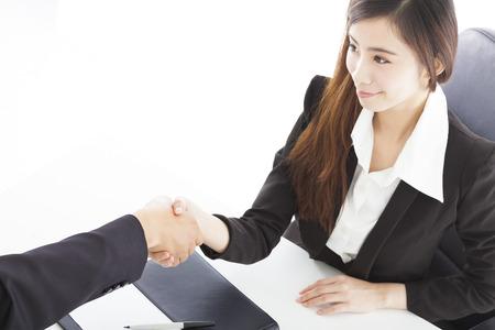 lächelnde Geschäftsfrau Händeschütteln mit Client in ihrem Büro