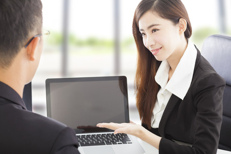 smiling Business woman showing at laptop and explaining a plan  photo