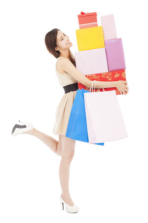 smiling young woman holding gift box and shopping bag photo
