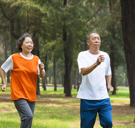 happy senior couple jogging together in the park photo