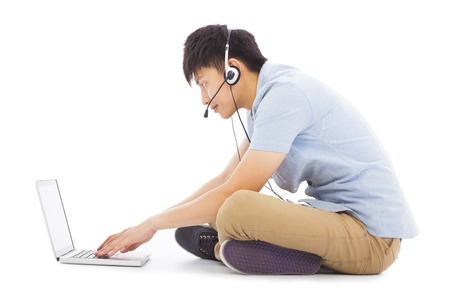 skype: Young man relaxing on floor and listening to music Stock Photo