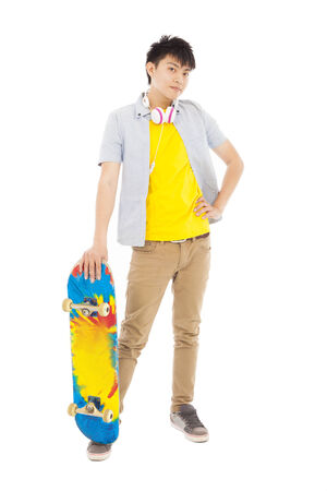 confident young man standing and holding a skateboard Stock Photo
