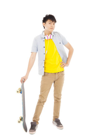 funky young man standing and holding a skateboard photo