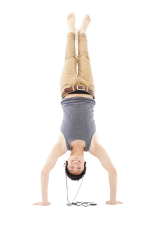 boy gymnast: young man doing a handstand against and listening music Stock Photo