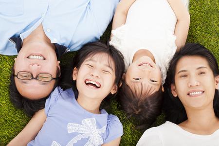 семья: счастливая семья, лежа на лугу вместе