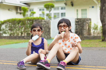 ice cream woman: little Girls  Eating Ice Cream and sitting before their house
