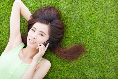 smiling girl lying down on a meadow  and talking by smartphone photo