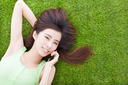 pretty girl lying down on a meadow  and talking by smartphone photo