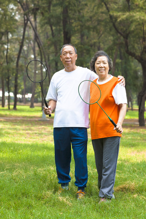 smiling older sibling and sister holding badminton racket   photo