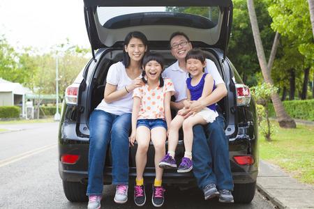 familias jovenes: familia feliz sentado en el coche y su casa detrás de Foto de archivo