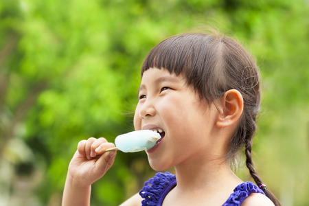 popsicle: happy little girl eating popsicle at summertime