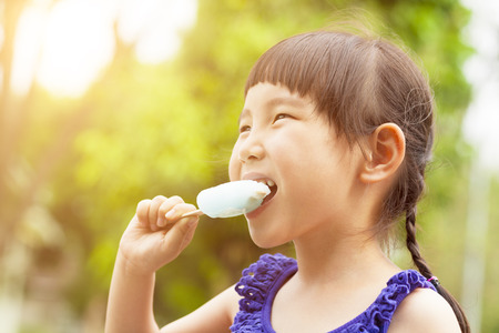 happy little girl eating popsicle at summertime with sunset  Stock Photo