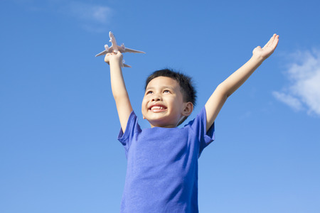 joyful little boy holding a toy with blue sky  photo