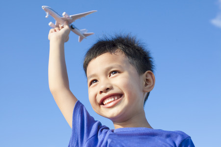 happy boy playing a airplane toy with blue sky  photo