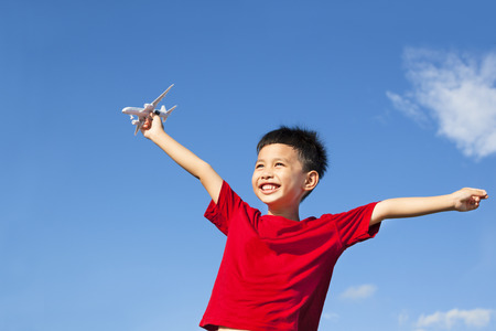 happy boy holding a airplane toy and open arms photo
