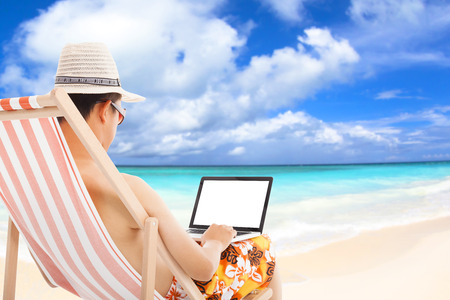 relaxed man sitting on beach chairs and using a laptop. photo