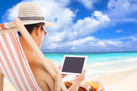 relaxed man sitting on beach chairs and touching tablet photo