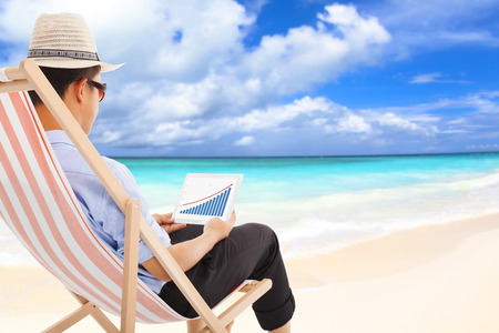 businessman sitting on beach chairs and look stock financial photo