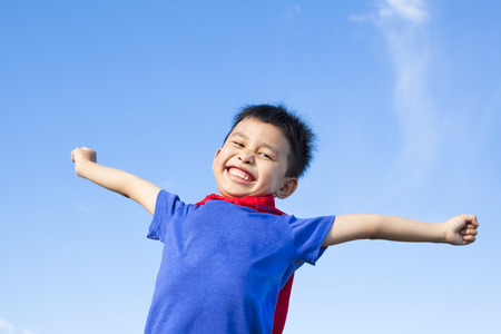 happy little boy imitate hero and open arms with blue sky