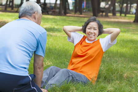 smiling senior grandmother doing sit-ups in the park Stock Photo