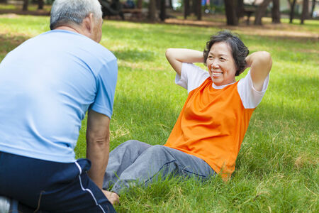 smiling senior grandmother doing sit-ups in the park Stock Photo - 28406557
