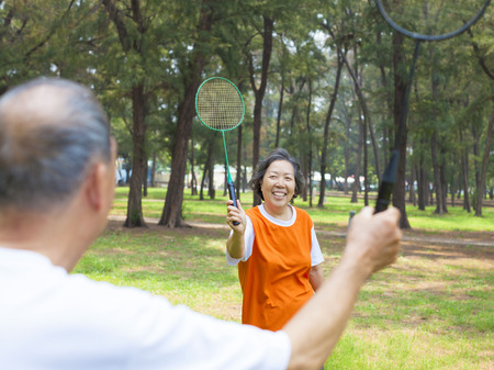 senior couple or friends playing badminton in the park photo