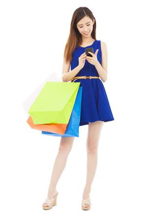 chicas compras: joven mujer con bolsas de la compra y tocar en el teléfono