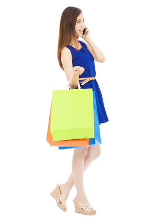 smiling young  woman holding shopping bags and talking on the phone photo