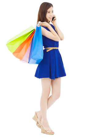 happy young  woman holding shopping bags and talking on the phone photo