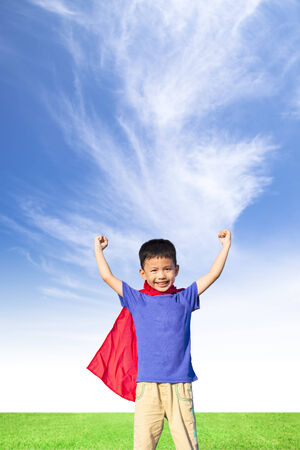 happy little boy imitate super hero and open arms with blue sky photo