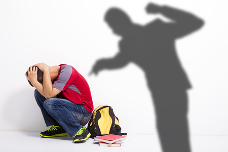 Man shadow attact   to terrified student with a fist  Stock Photo