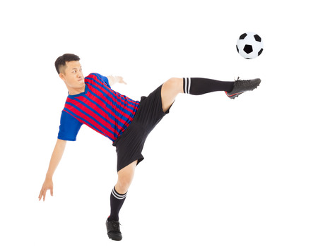 football socks: Young soccer player Steals the flying ball Stock Photo