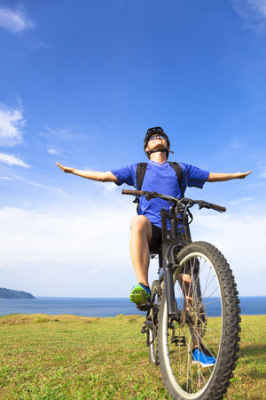 close-up man sitting on a  mountain bike and open arms to relax photo
