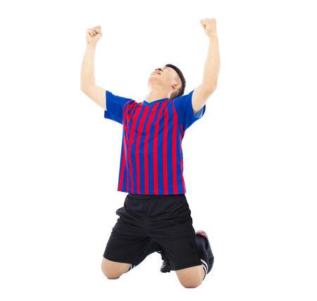 arrodillarse: joven jugador de fútbol y las manos levantadas para celebrar ganador