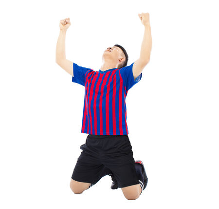 kneel: young soccer player and raised hands to celebrate winner