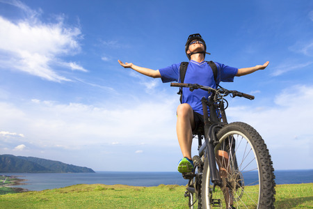 young man sitting on a  mountain bike and open arms to relaxing photo