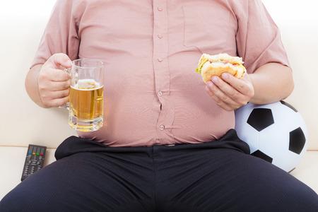 Hombre de negocios gordo que come la comida y la cerveza y sentado en el sofá