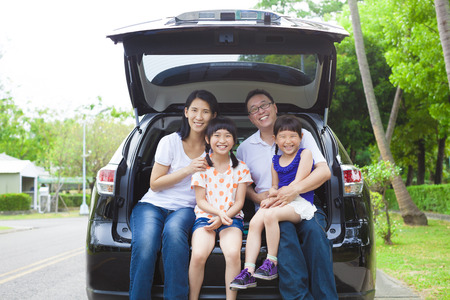 vacations: happy family sitting in the car and their house behind Stock Photo