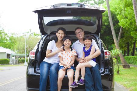 resor: lycklig familj sitter i bilen och deras hus bakom