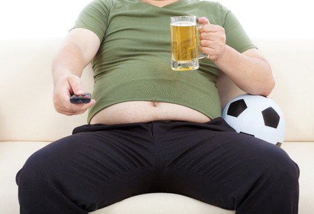 fat man drinking beer  and sitting on sofa to watch TV photo