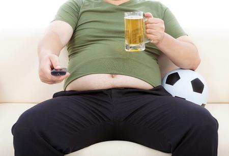 ver television: hombre gordo bebiendo cerveza y sentado en el sof� para ver la televisi�n Foto de archivo
