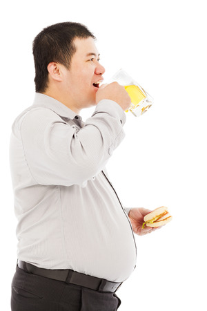 fat business man drinking beer mug and eating hamburger photo