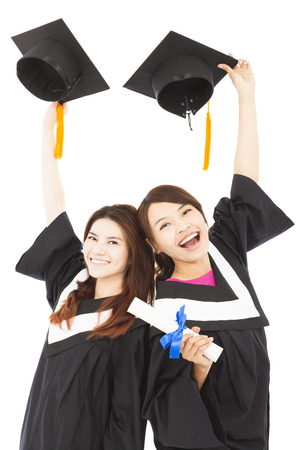 two happy young graduate students holding hats and diploma photo