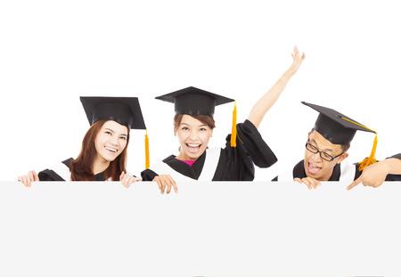 felices estudiantes graduados jóvenes con la tarjeta en blanco