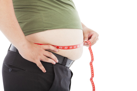 over weight: fat man use scale to measure his waistline Stock Photo