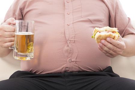 obesidad: hombre de negocios la celebración de grasa jarra de cerveza y hamburguesas Foto de archivo