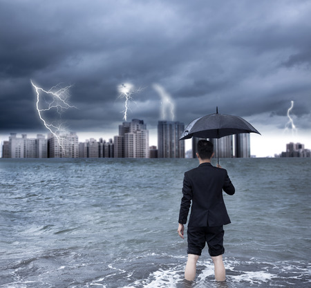 thundershower: business man holding an umbrella with thundershower background Stock Photo