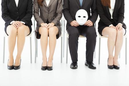 falso: la gente de negocios esperando la entrevista de trabajo con una extraña máscara Foto de archivo