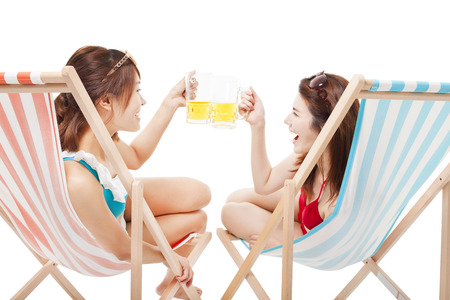 two sunshine girl holding beer cheers  on a beach chair photo