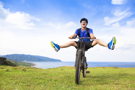 kenting: funny young backpacker riding a bicycle on a meadow